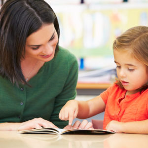Elementary Pupil Reading With Teacher In Classroom